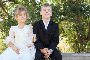 happy little brother wearing black suit and sister wearing beaut